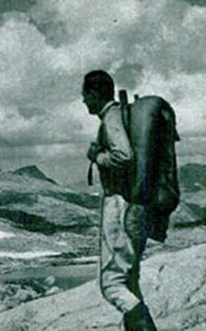 vintage man backpacking in mountains overlooking valley
