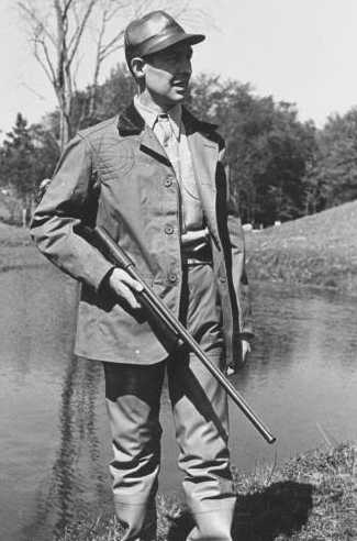 vintage 1950s man hunting with gun near pond