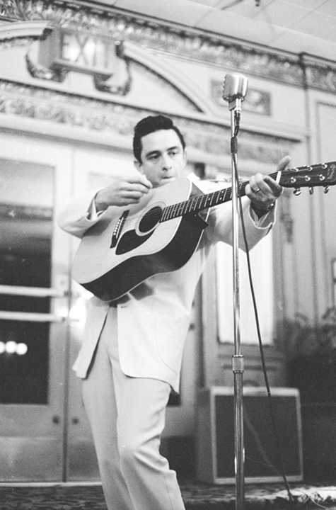 young johnny cash playing guitar into microphone