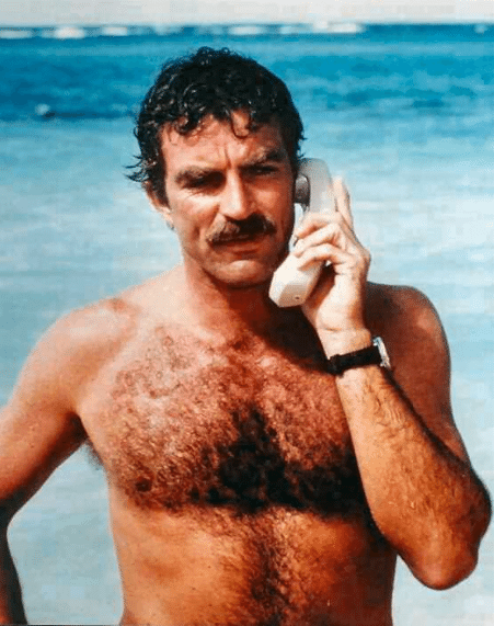 Tom Selleck hearing phone in front of ocean.