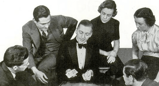 Vintage people showing magician of cards trick.