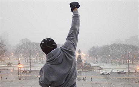 Man raising his hand in snow falling.
