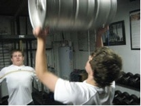 strongman odd object strength training lifting kegs