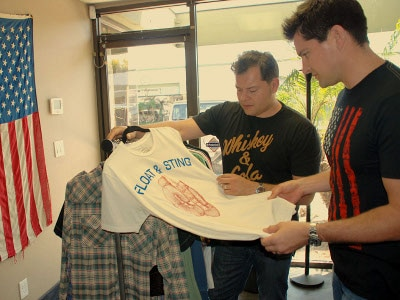 Mike Anderson and John Anderson seeing finishing of t shirt.