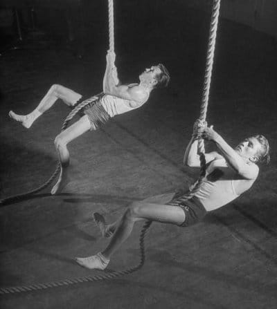 Vintage young men climbing ropes in a gym.