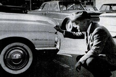 vintage man 1940s 1950s looking at car crouching