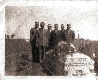 Gentlemen attending funeral at graveyard.
