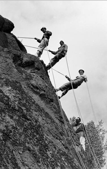 Vintage men climbing on mountain with ropes cliff.