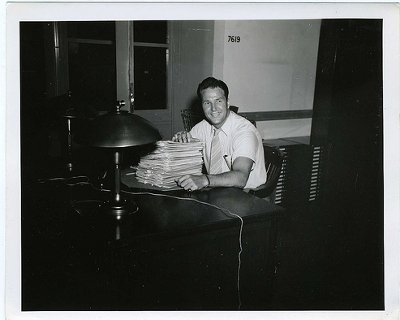 Vintage man at desk with pile of paperwork.