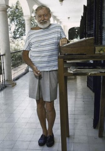 Ernest Hemingway older man with standing desk in shorts and sock-less.