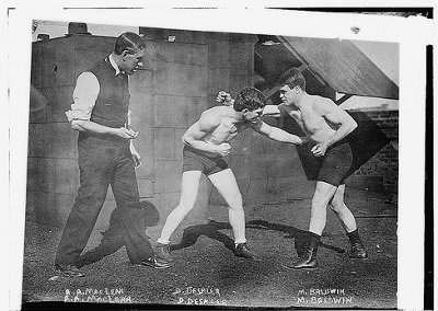 Vintage young men photo while boxing from early 20th century.