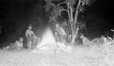Vintage campers young men sitting around campfire.