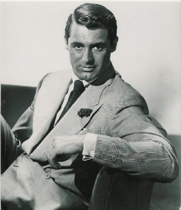 A vintage man wearing suit with Boutonniere sitting on a sofa.