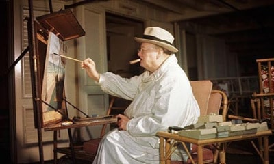 Winston churchill painting in art studio and smoking cigar.