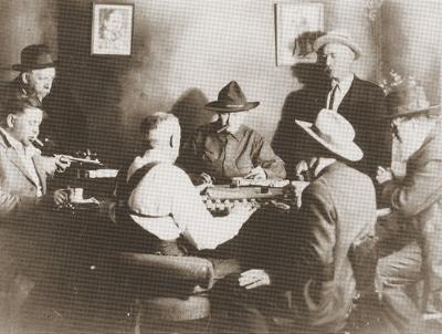 Vintage men cowboys playing poker game while smoking cigars.