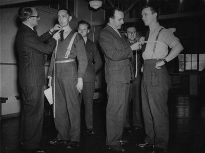 Vintage tailors measuring the men's chest and neck.