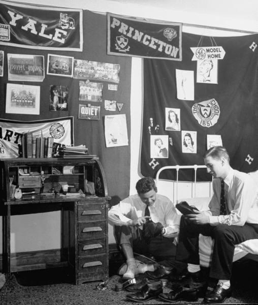 Vintage college men Polishing shoes in dorm room.