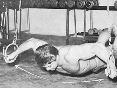 Vintage boy doing body weight ring exercise push up.