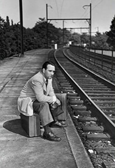 vintage man in suit sitting alone at railroad tracks