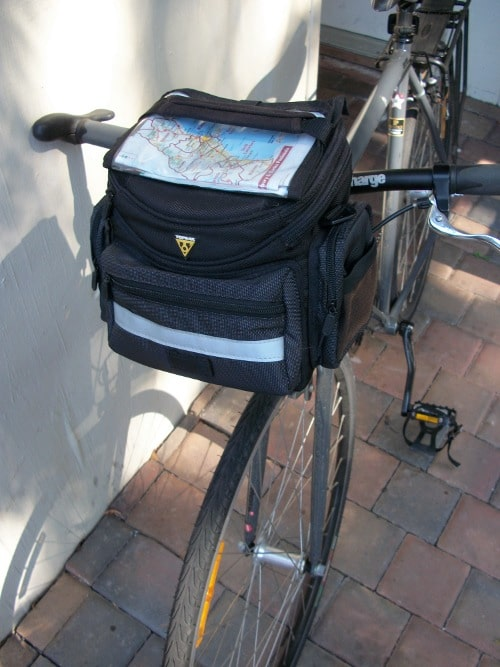 Handbag packed with front handle of bicycle.