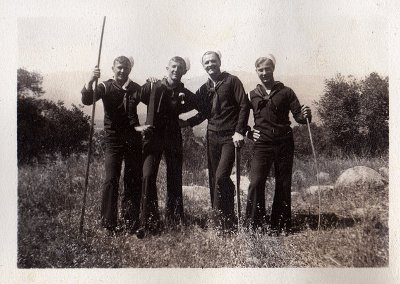 Vintage men hiking with walking sticks in forest.