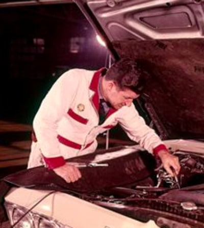 Vintage mechanic working under car hood.