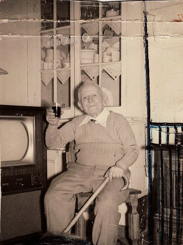 vintage older man sitting with cane raising glass