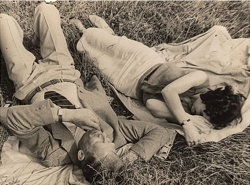 vintage older couple laying on blankets in grass
