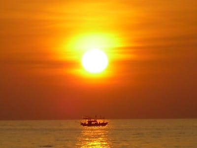 fishing boat on ocean sun setting bright orange