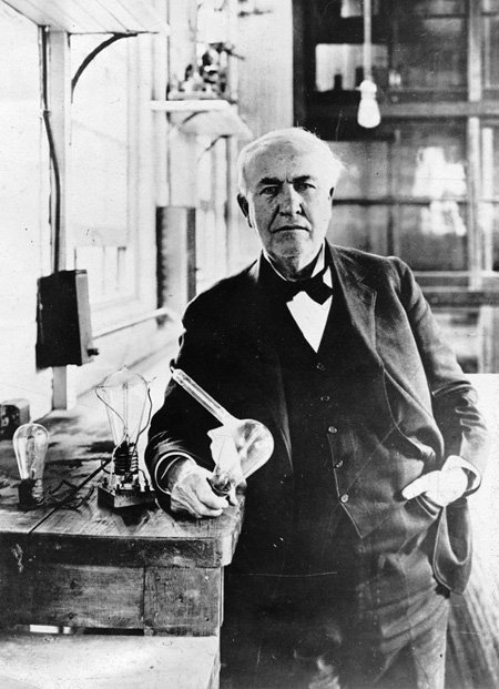 Vintage Thomas Edison standing in workshop and holding light bulb.
