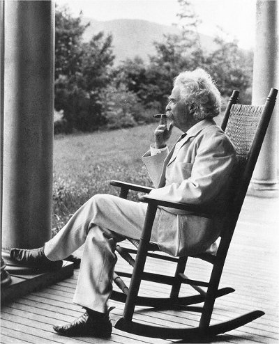 Vintage Mark Twain sitting on chair and smoking cigar.
