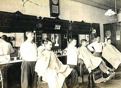 Vintage men getting haircut at barbershop.