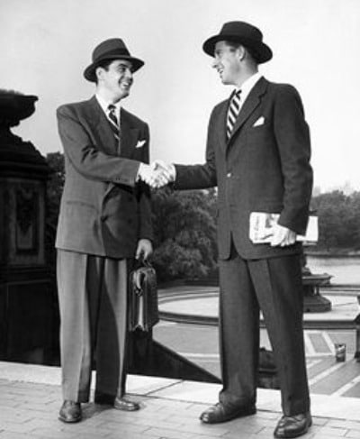 Two formally dressed men smiling while shaking hands.