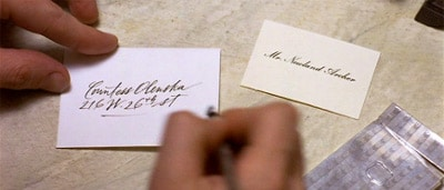 A man writing on calling card with pen.