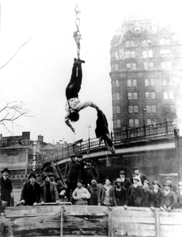 Harry Houdini hanging upside down off the ground while removing jacket.