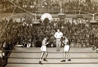amateur boxing match fighters in ring big crowd