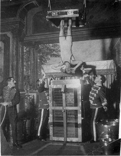 harry houdini hanging upside down lowered into container