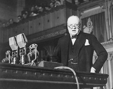winston churchill giving speech in parliament glasses and suit