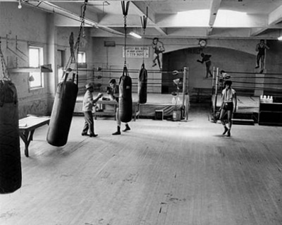Boxer having practice session with trainer in gym.