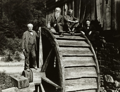 Thomas Edison and his friends sitting on the mill wheel.