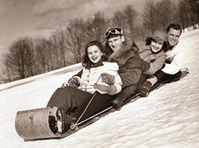 vintage couples sledding down snowy hill