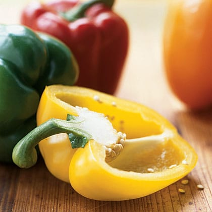 Yellow, green, red and orange bell peppers on cutting board.