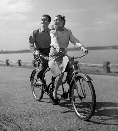 Couple sitting on bicycle and giving smile pose.