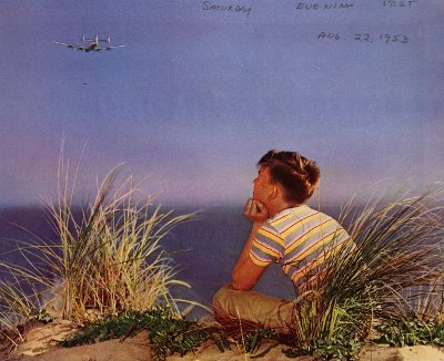 Boy looking at airplane flying in the sky.