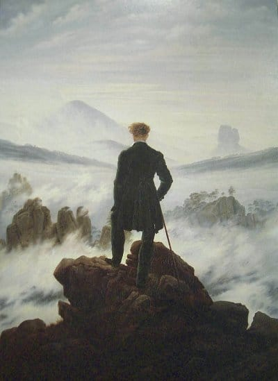 Formal dressed up man standing at the edge of cliff holding a stick.