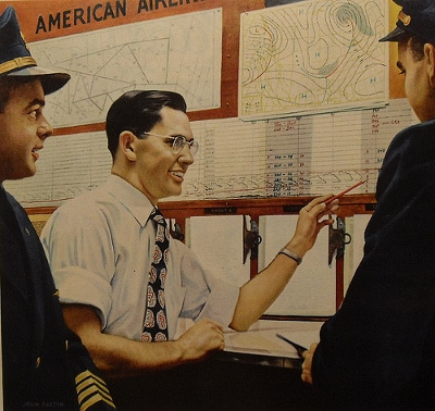 American airlines officer explaining maps to pilots.