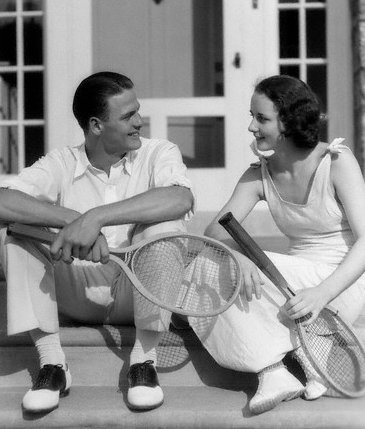 vintage man woman sitting with wooden tennis racket