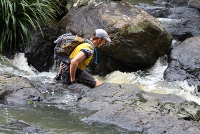 adventure race racing man wading in river rapids