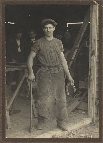 vintage blacksmith in shop with apron horseshoe in hand
