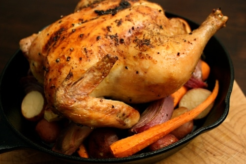 homemade roast chicken over veggies cast iron